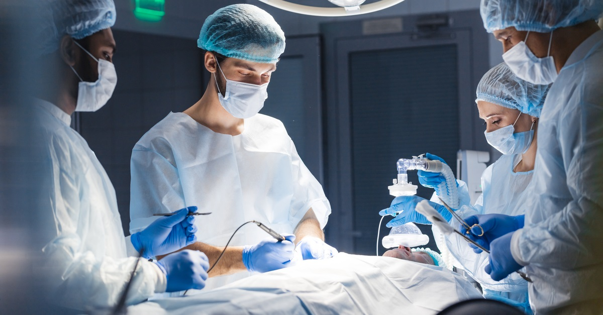 Group of surgeons inside the operating room helping patient to survive.