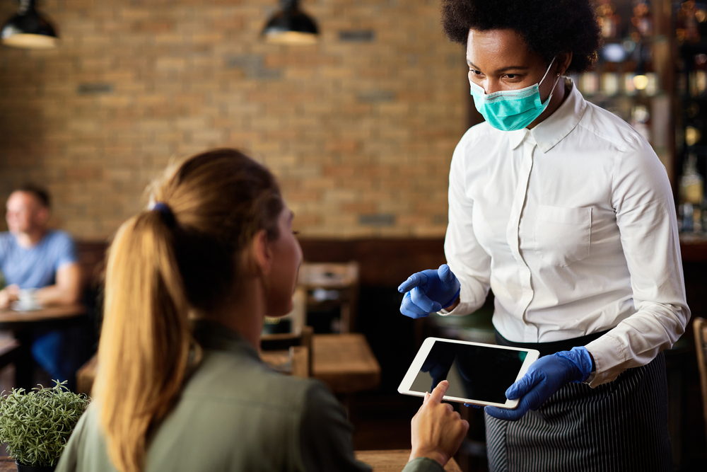 Waitress working with facemask on during the Covid-19 pandemic..