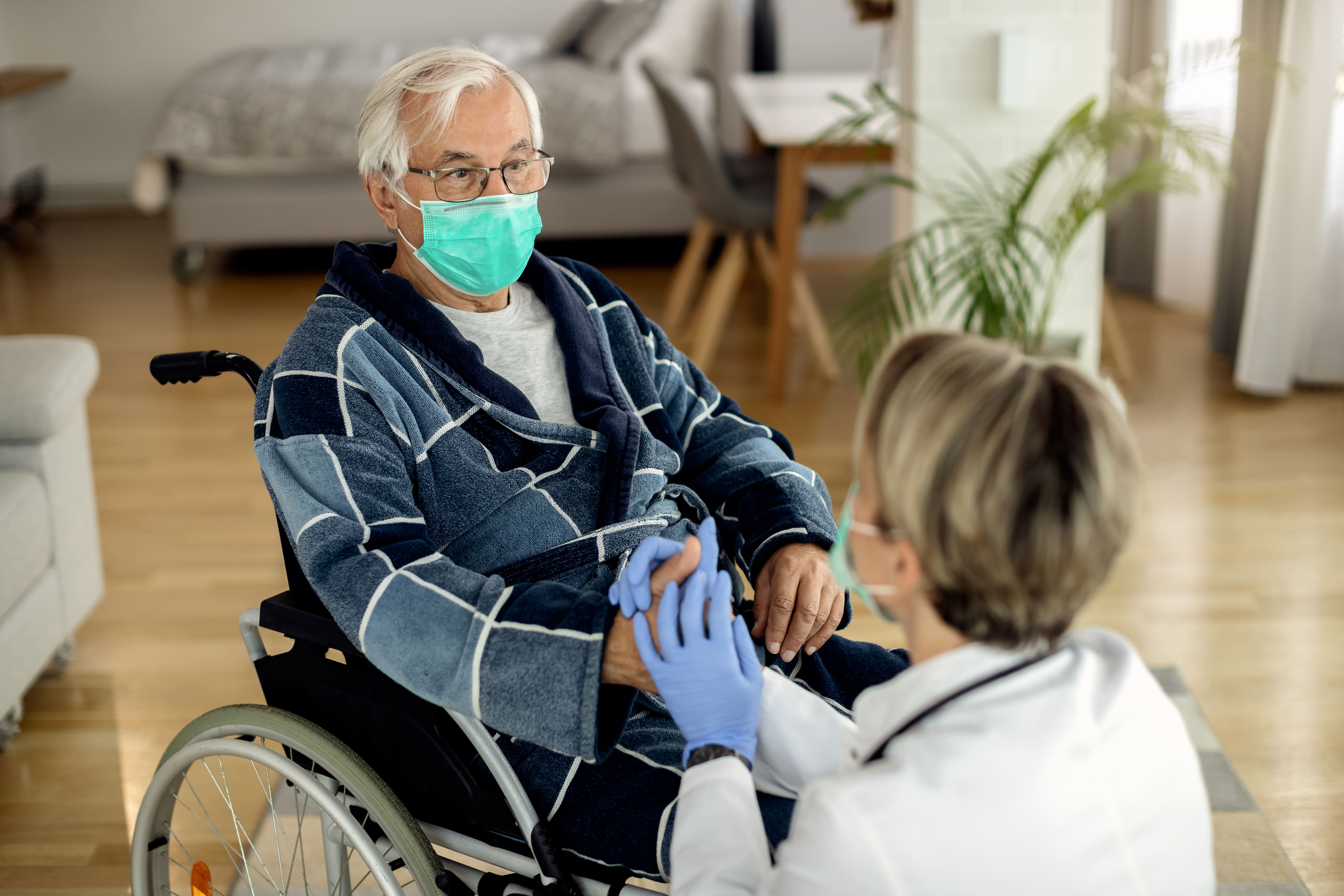 Veteran at a nursing home speaking with his doctor.